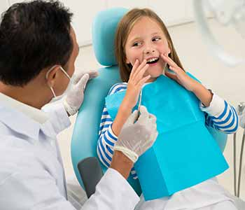 Image of a baby girl showing her mouth to a dentist